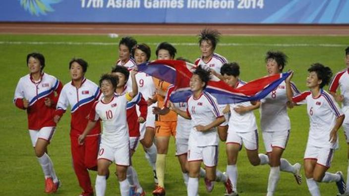 North Korea's players celebrate with their national flag after winning against Japan during their women's final soccer match at the Munhak Stadium during the 17th Asian Games in Incheon